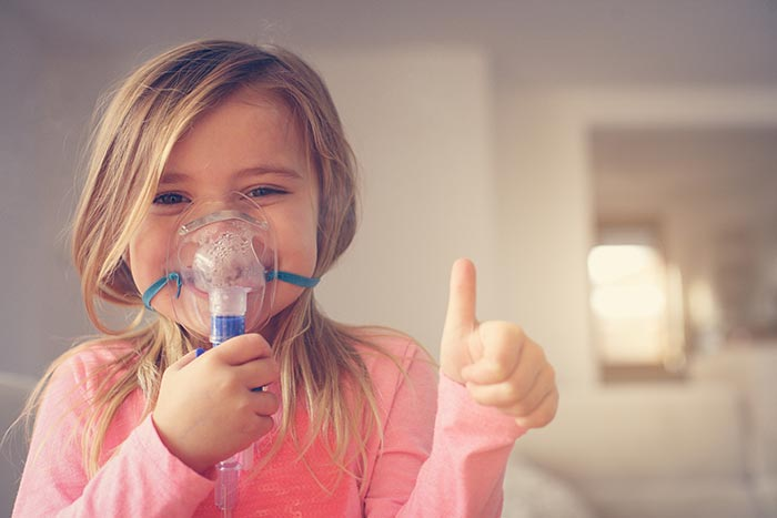 little girl using inhaler