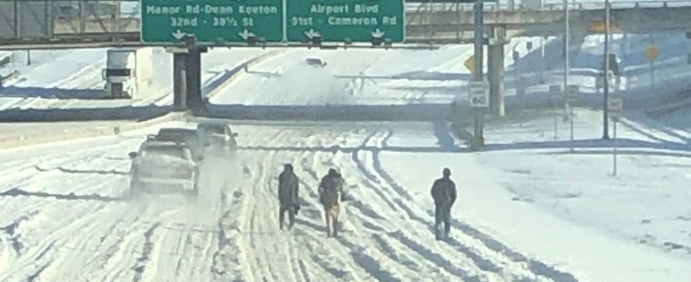 people waling on snowy interstate