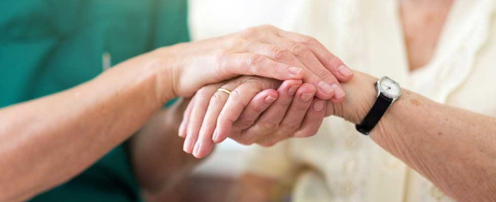 nurse holding older woman's hand