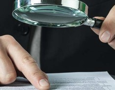 white male hand pointing to legal copy and holding a magnifying glass looking for loopholes
