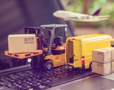 toy forklift and van on keyboard to illustrate supply chain