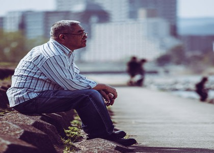 Asian senior adult male sitting alone in a park looking pensive