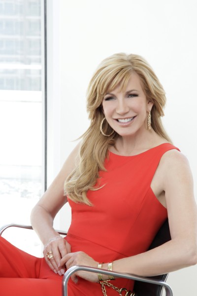 Leeza Gibbons seated in chair in red dress